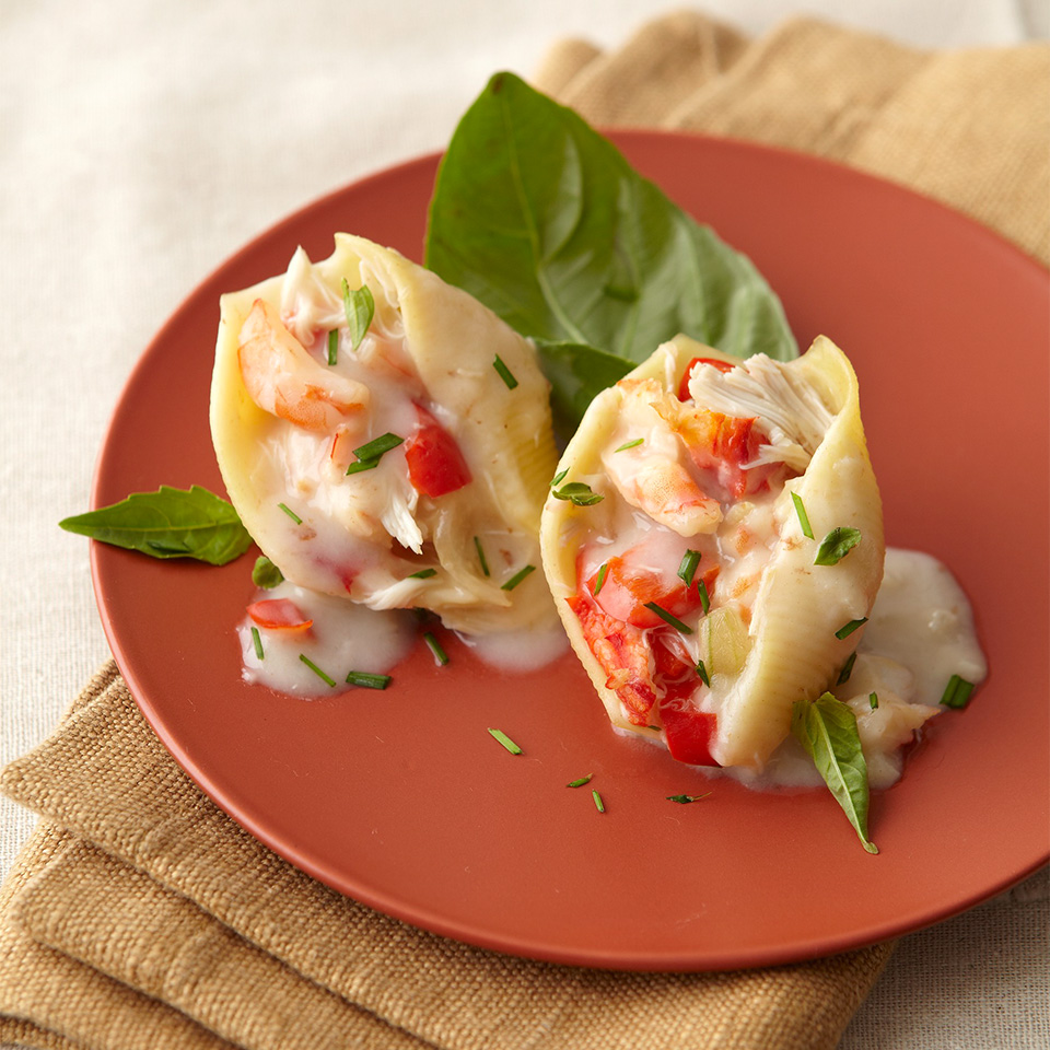 two stuffed shells with shrimp on a red plate