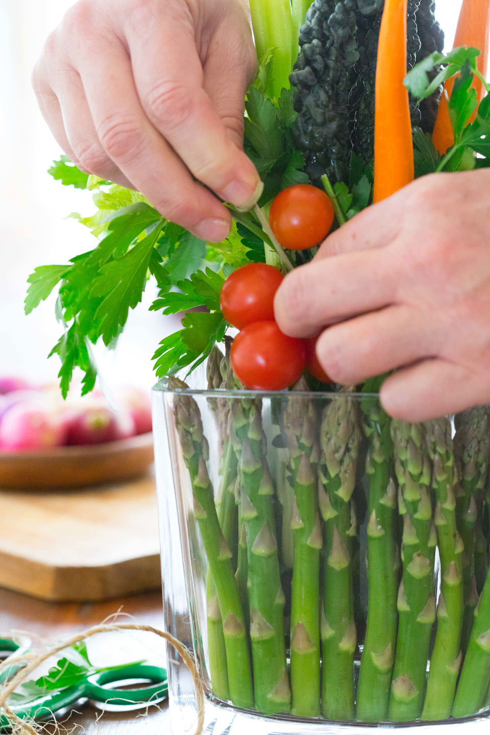 Decorate the arrangement by skewering cherry tomatoes with a bamboo pick pressing into the kale and parsley