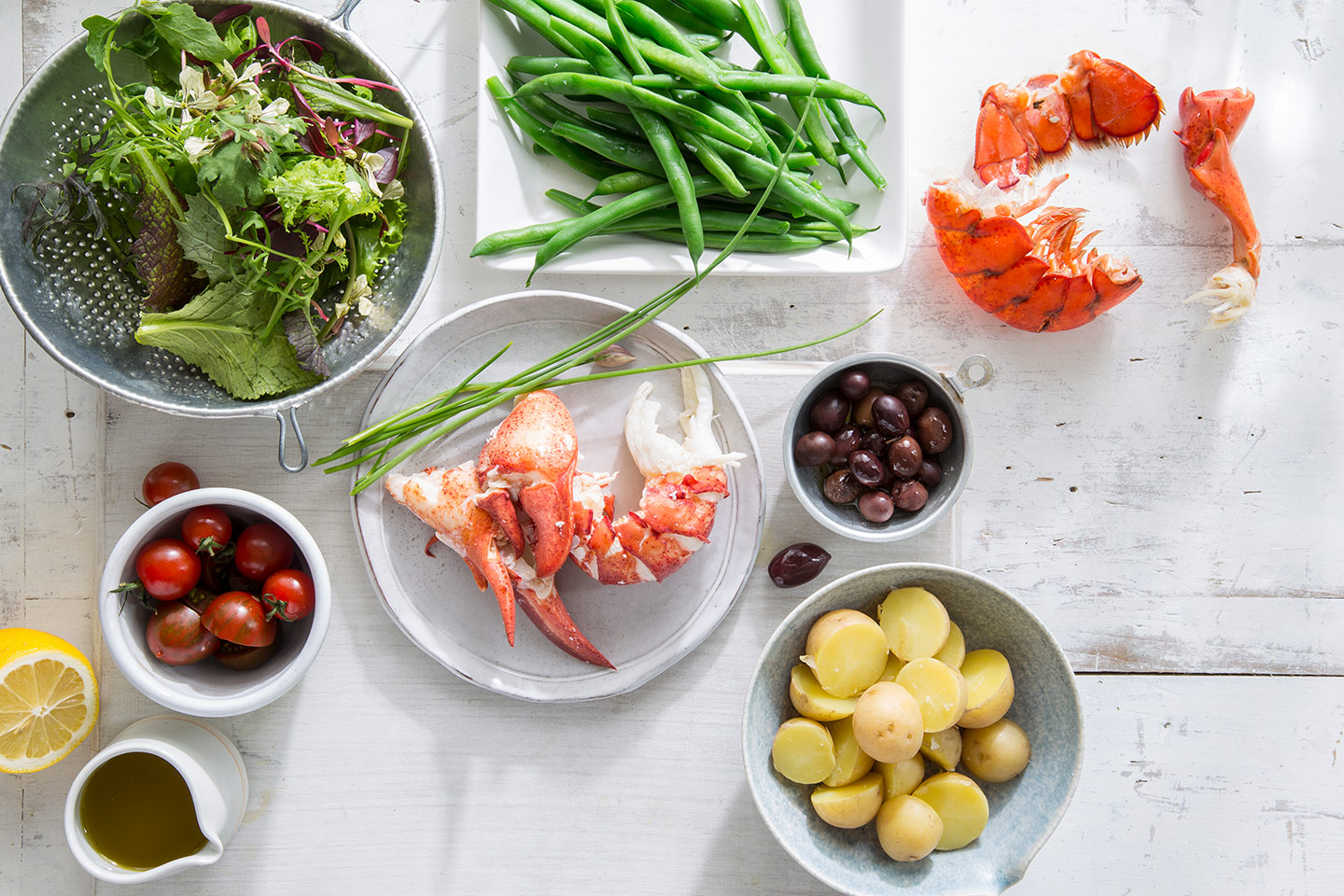shelled lobster on a table with fresh salad ingredients