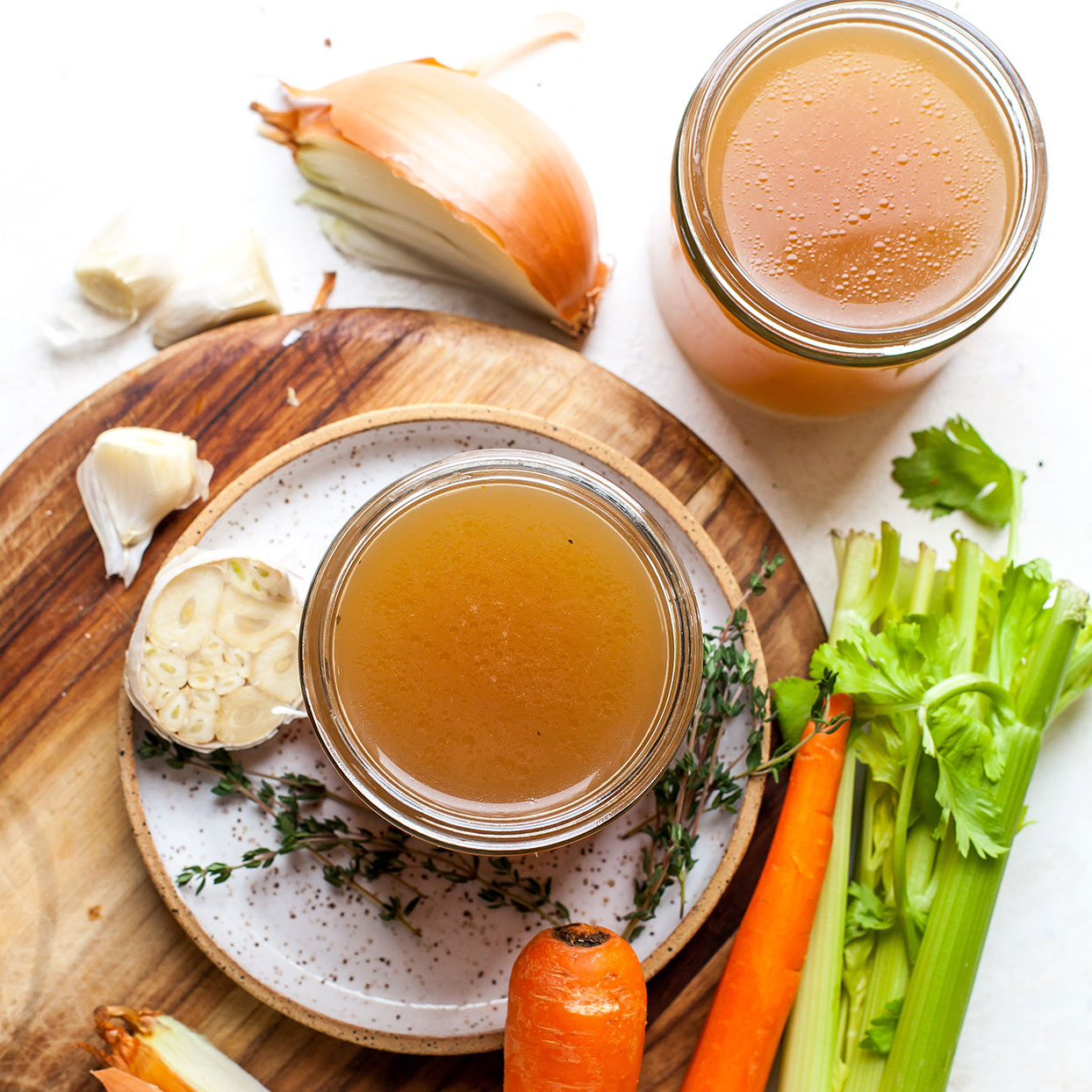 photo of beef bone broth in clear bowl with carrots and celery