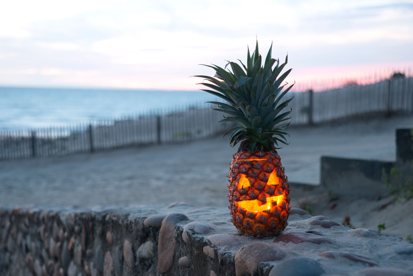 Pineapple jack-o'-lantern on a beach