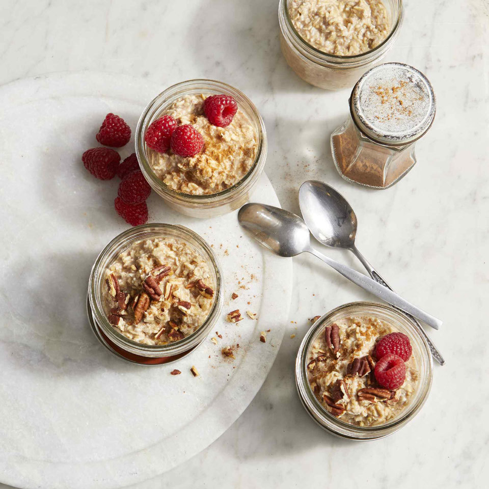 cinnamon roll overnight oats shot overhead in mason jars with raspberries and pecans on top