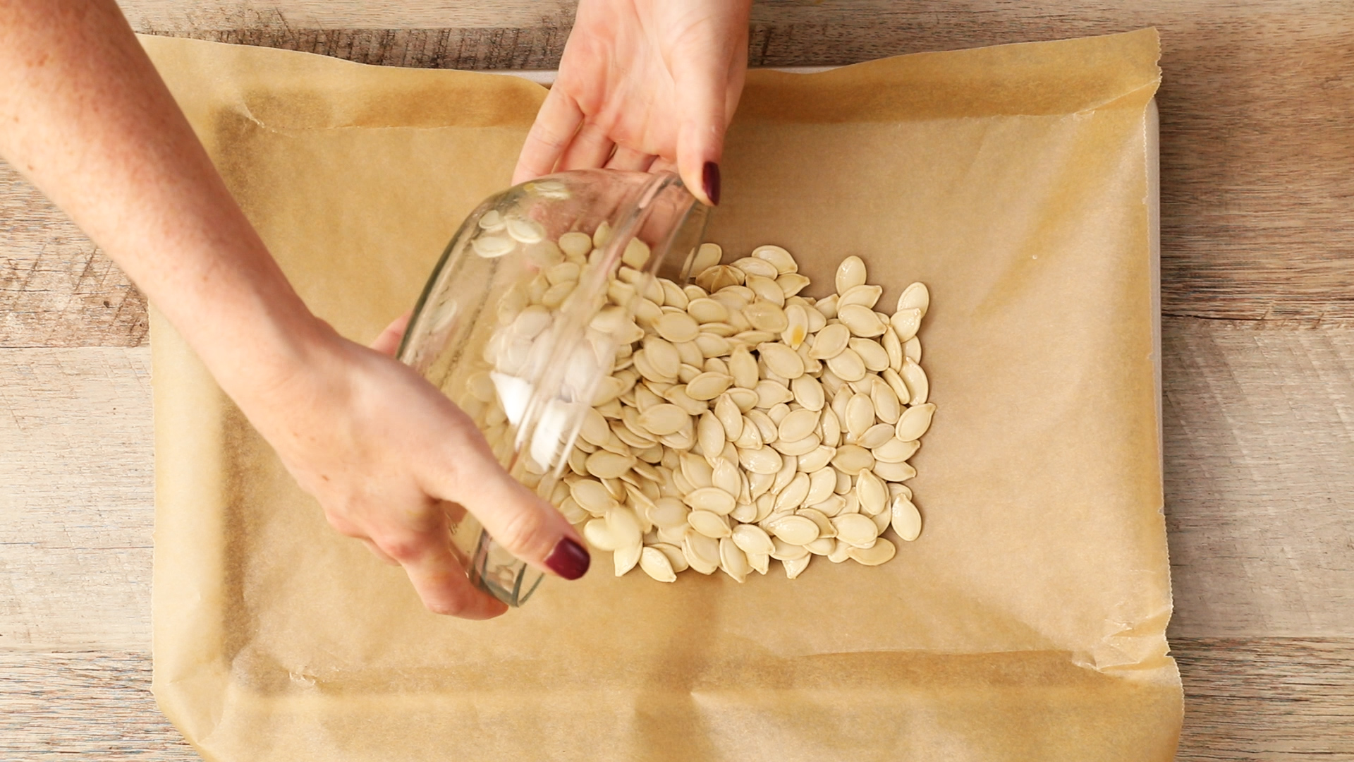 pouring pumpkin seeds on a roasting pan