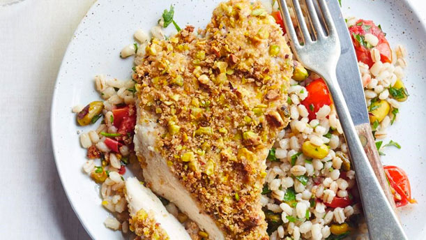 crusted chicken on a plate with grains, herbs and veggies