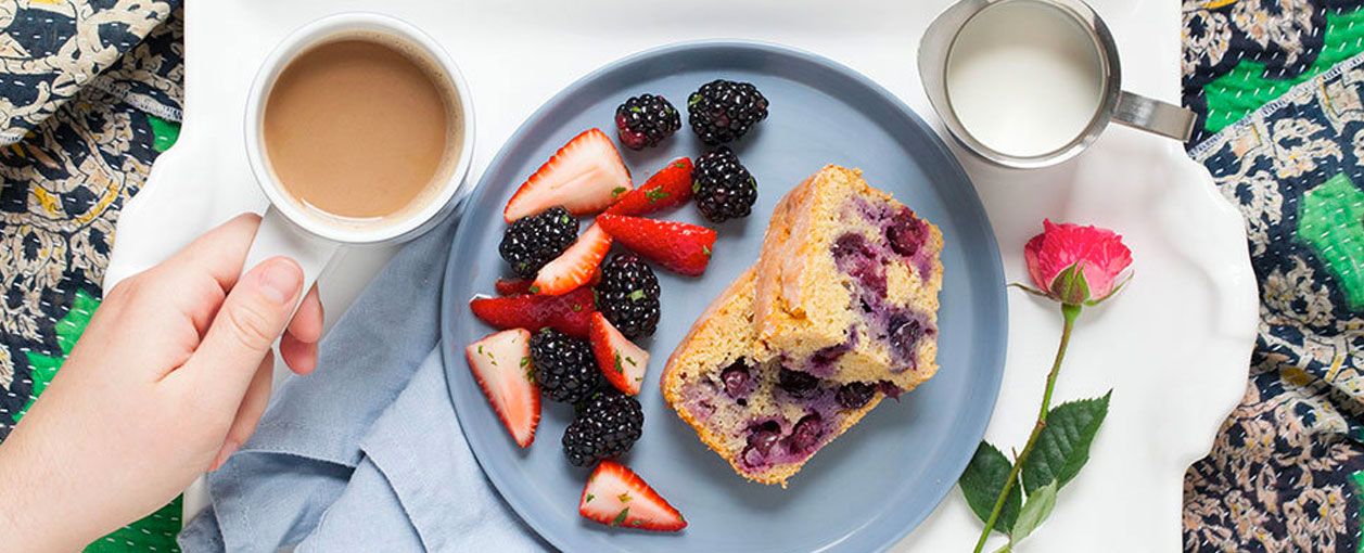 breakfast in bed for mothers day - coffee, cake, fruit on a tray