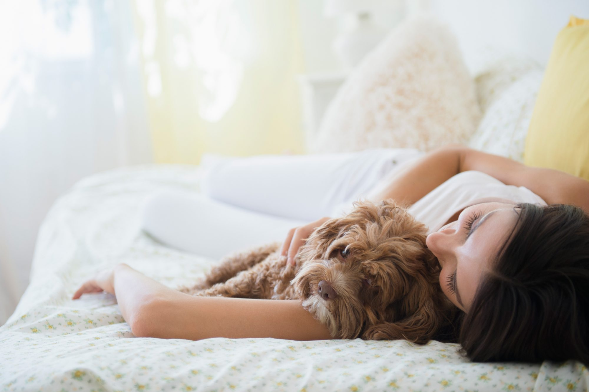 woman hugging brown dog in bed