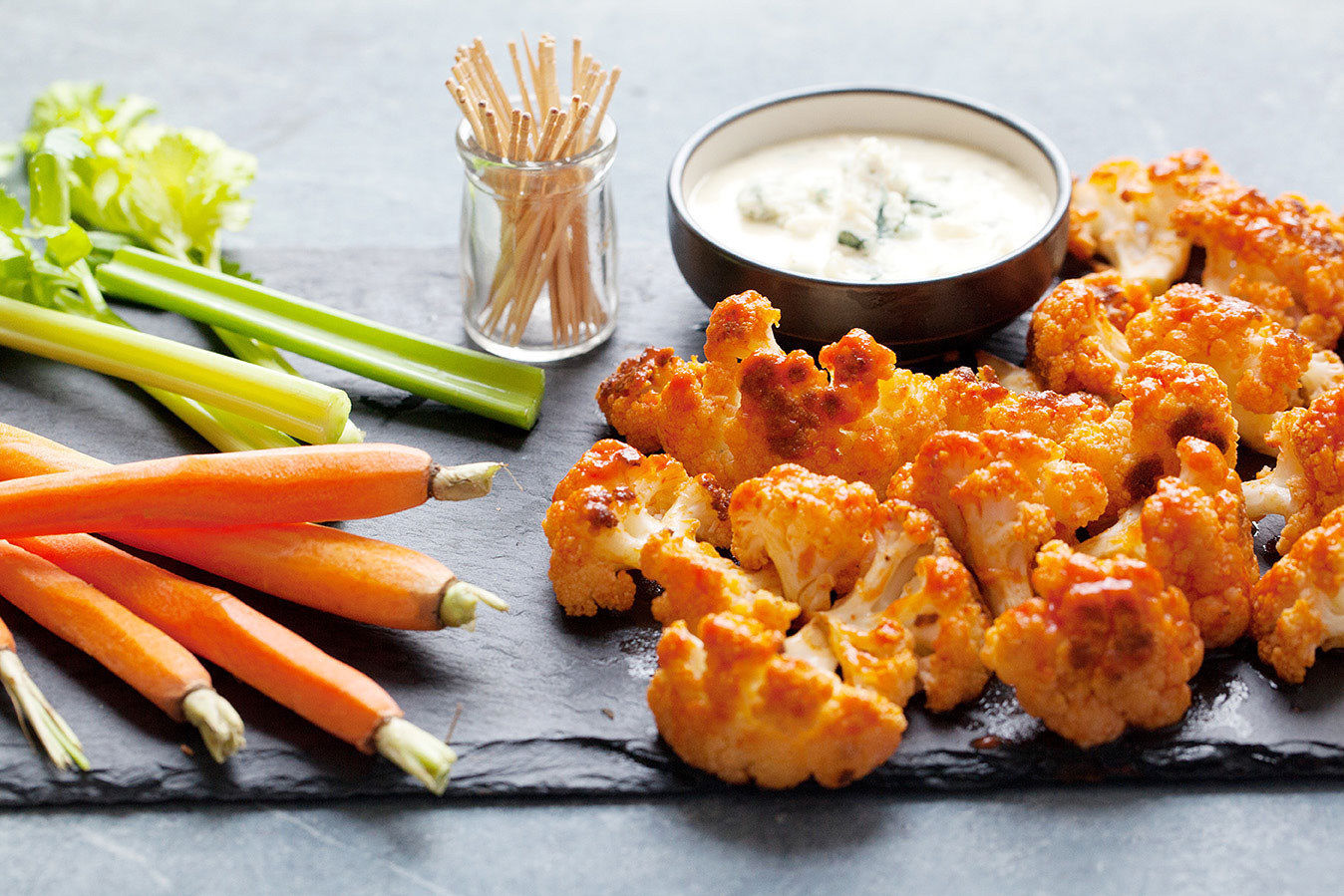 buffalo cauliflower on a platter with celery and carrots