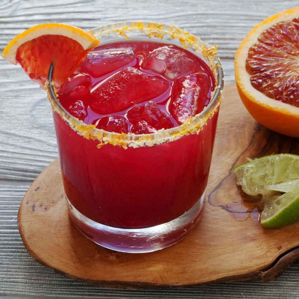 red colored drink in a glass with blood orange slice garnish