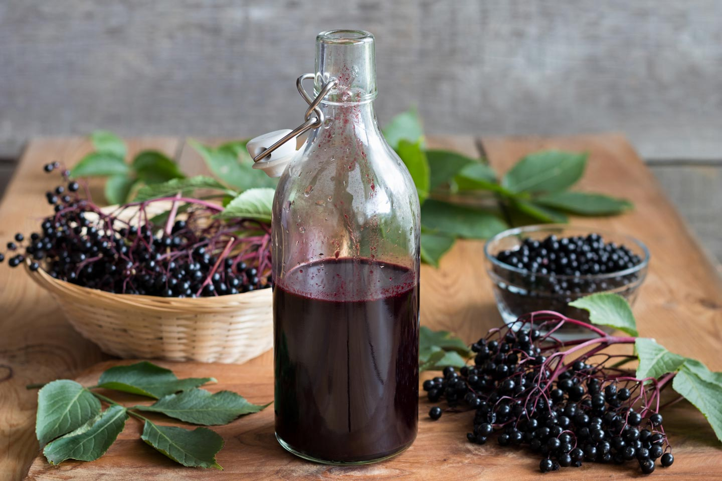 Elderberry syrup in a glass jar with elderberry bundles placed around it