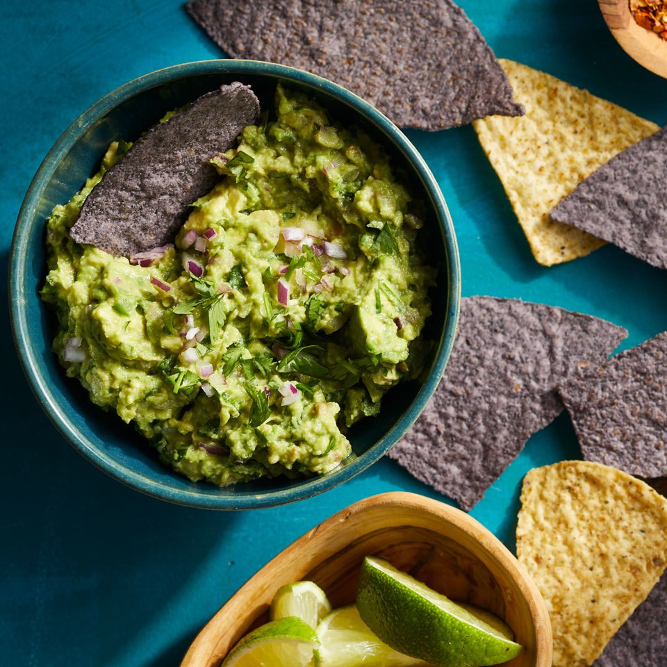 overhead shot of Almost Chipotle's Guacamole in blue bowl on blue background with chips