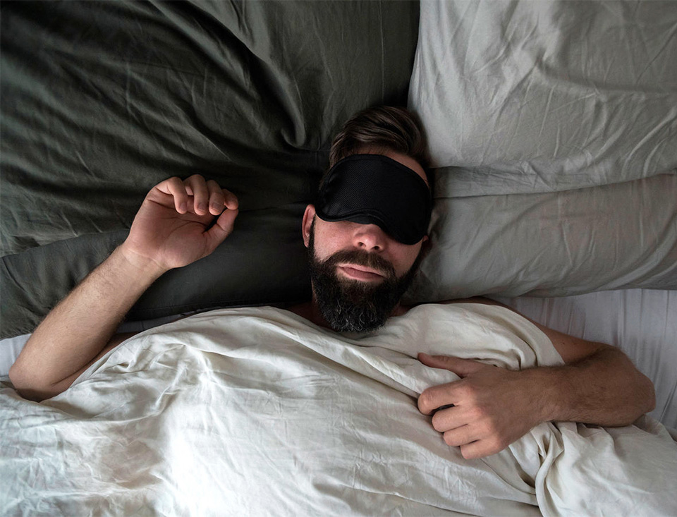 man asleep in bed with eye mask