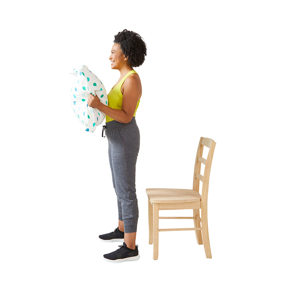 woman standing with pillow chair squat