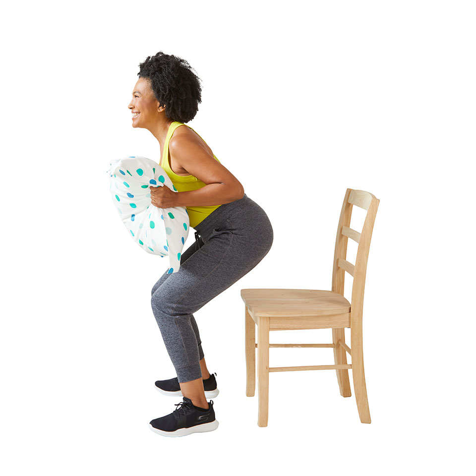 woman squatting with pillow over chair