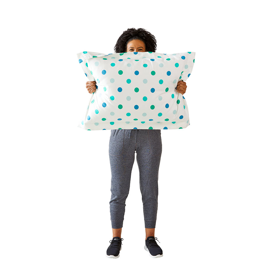 woman doing shoulder circles holding pillow in front of her