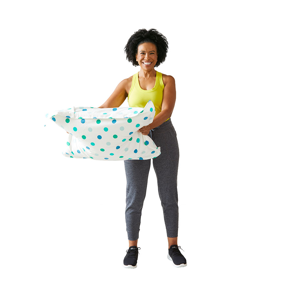 woman doing shoulder circles with pillow to her side