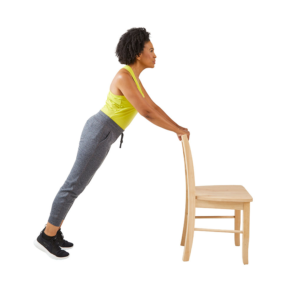 woman doing pushup against chair upright