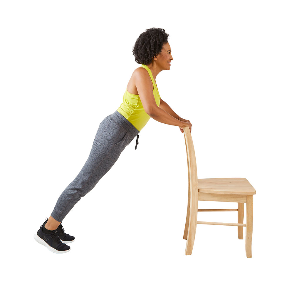 woman doing pushup against chair bent other