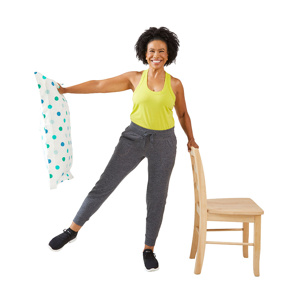 woman holding up pillow with hand on chair and leg raised