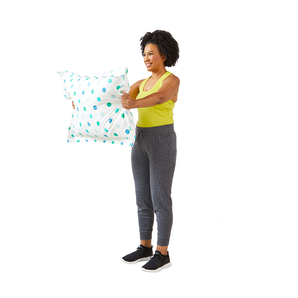woman holding out pillow preparing to raise knees