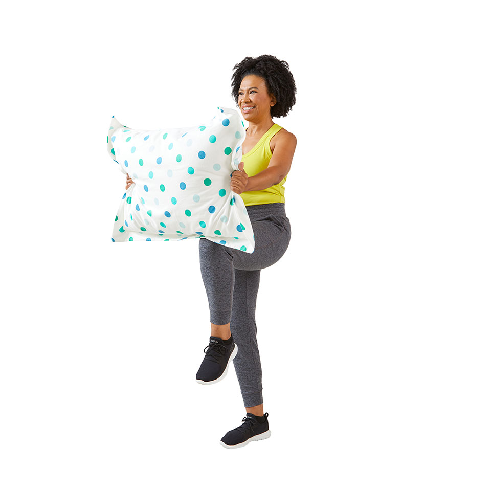 woman raising knee while holding pillow in front of her