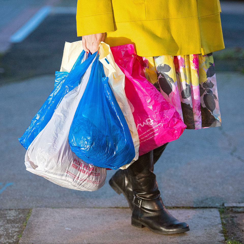 woman carrying plastic shopping bags