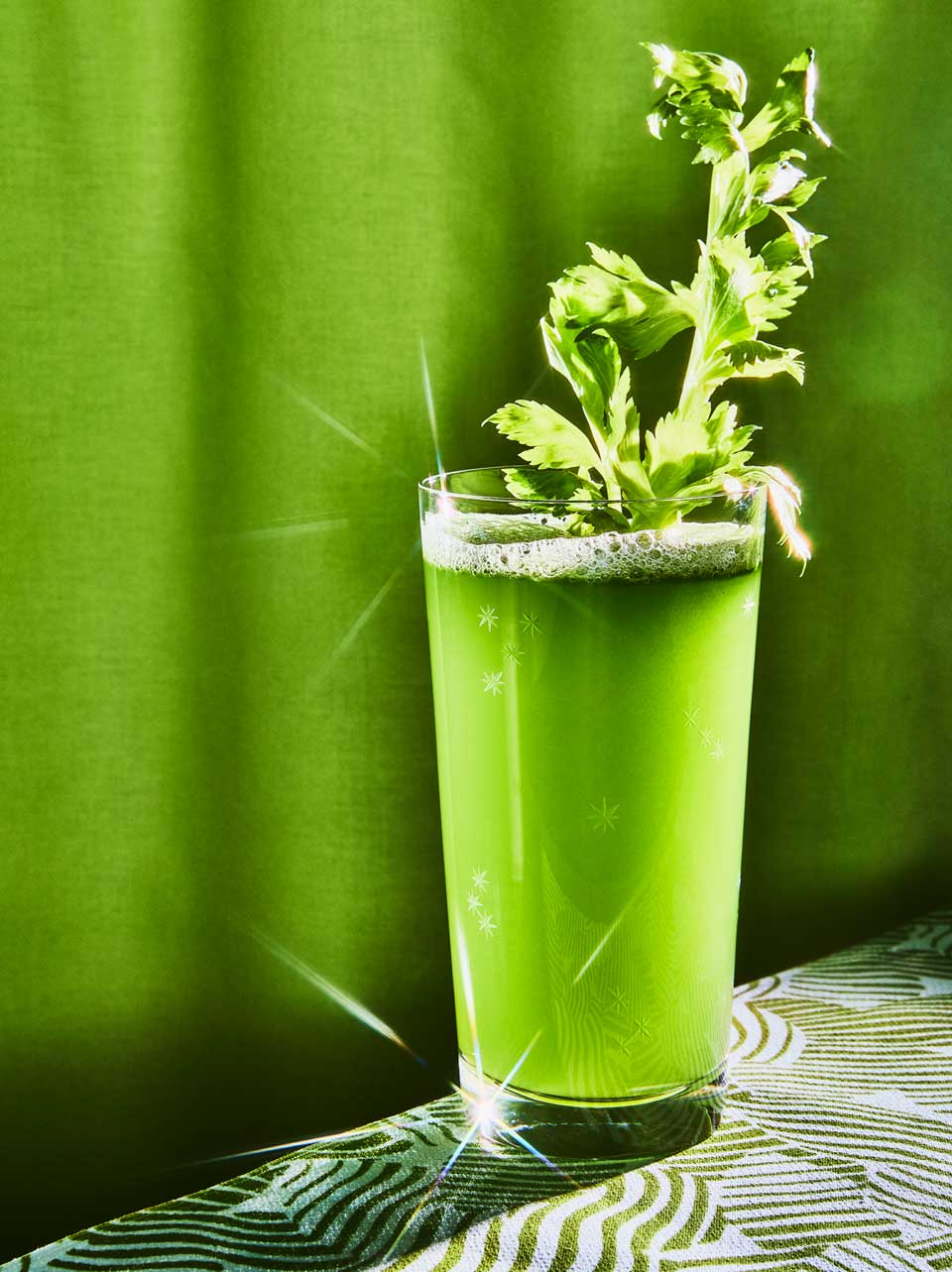 celery juice in sparkling glass on green background with stalk of celery in cup