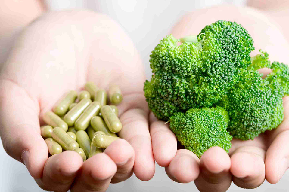 hands holding broccoli and dietary supplements