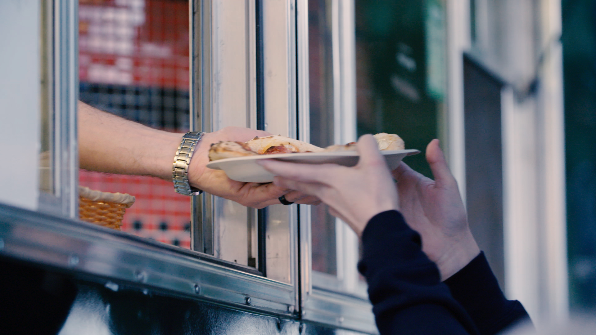 hands giving a plated slice of pizza to a customer's hands from the window of a food truck