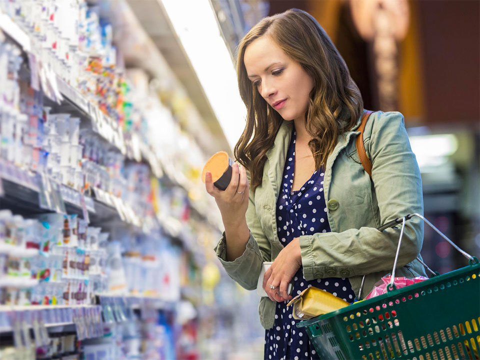 woman reading the nutrition facts on a food container in a grocery store