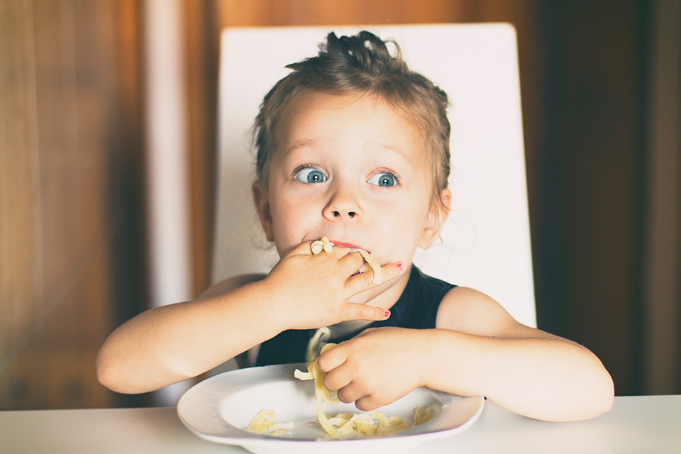 child eating pasta with hands