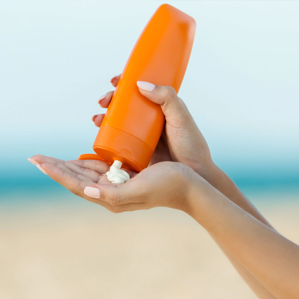 hands holding bottle of sunscreen