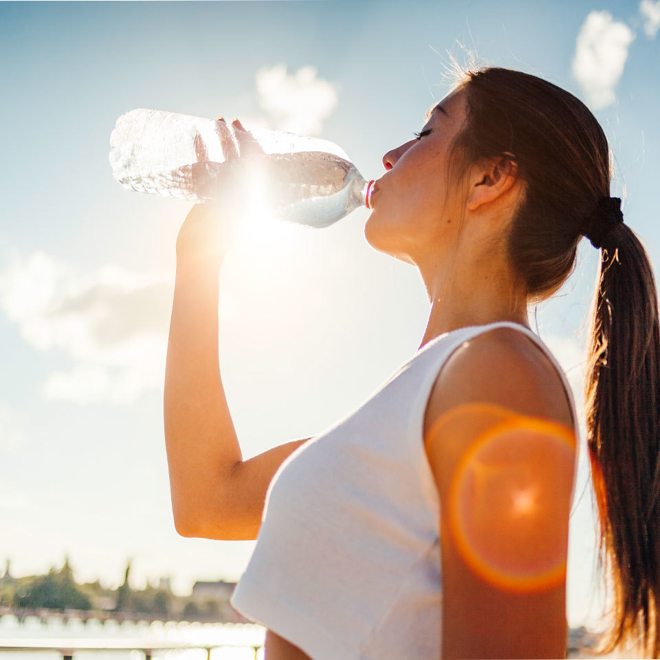 woman drinking bottled water in sun