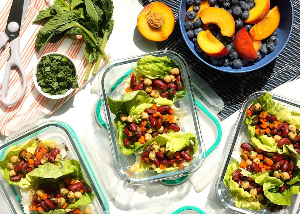 summer lunch prepped meals in containers with bowl of blueberries and peaches