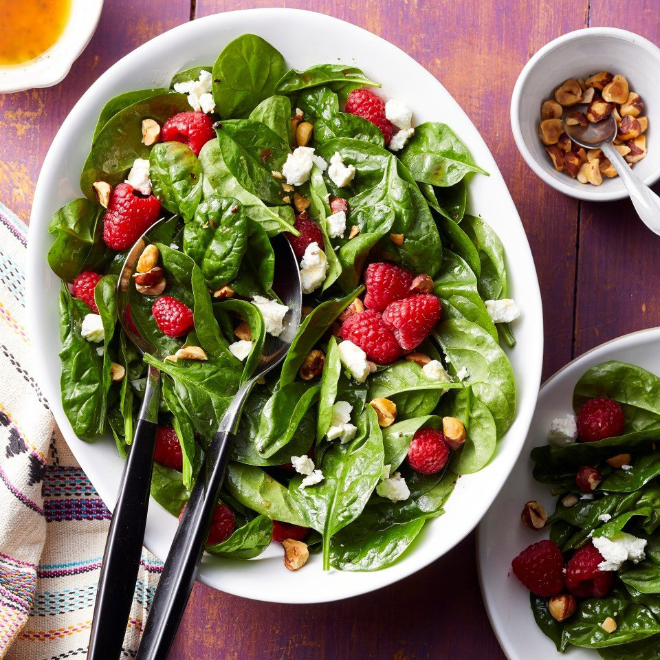 green salad with berries in a white bowl