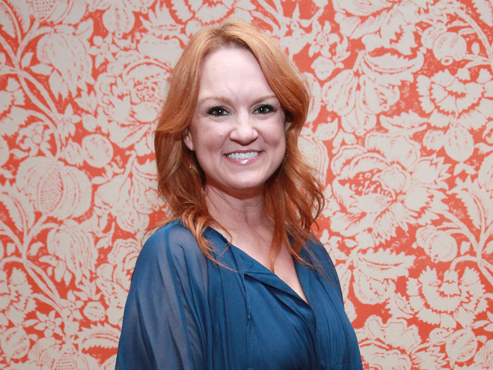 Ree Drummond standing against a floral wallpaper background