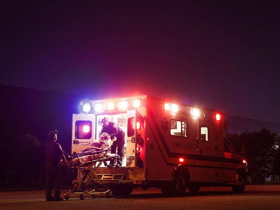 EMTs pushing a stretcher into an ambulance