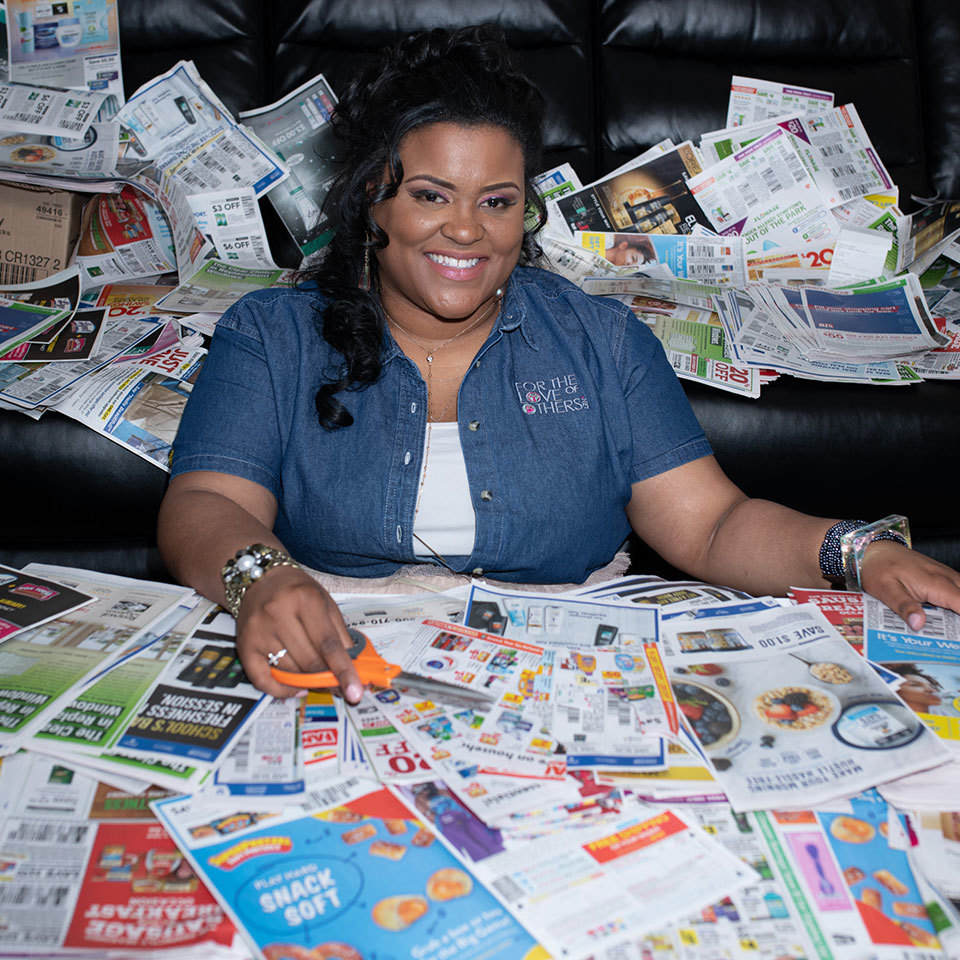 Lauren Puryear surrounded by coupons in her living room