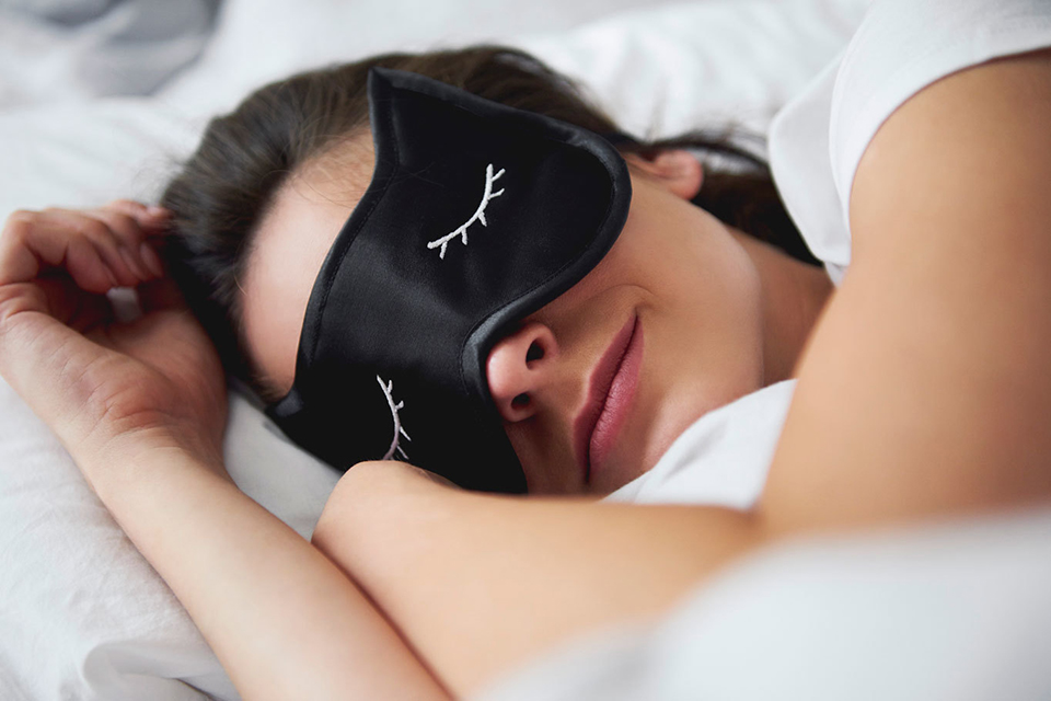 woman lying in bed with a sleep mask on