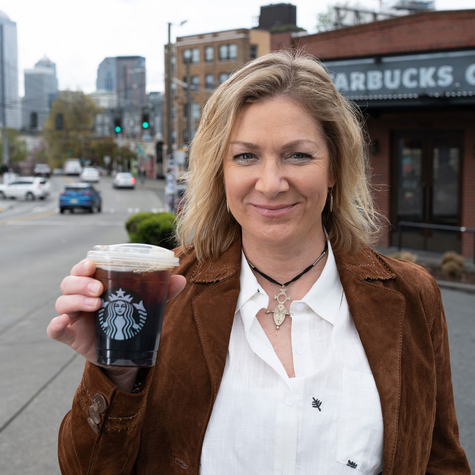 Rebecca Zimmer holds new straw-free Starbucks cup in front of Seattle Starbucks shop