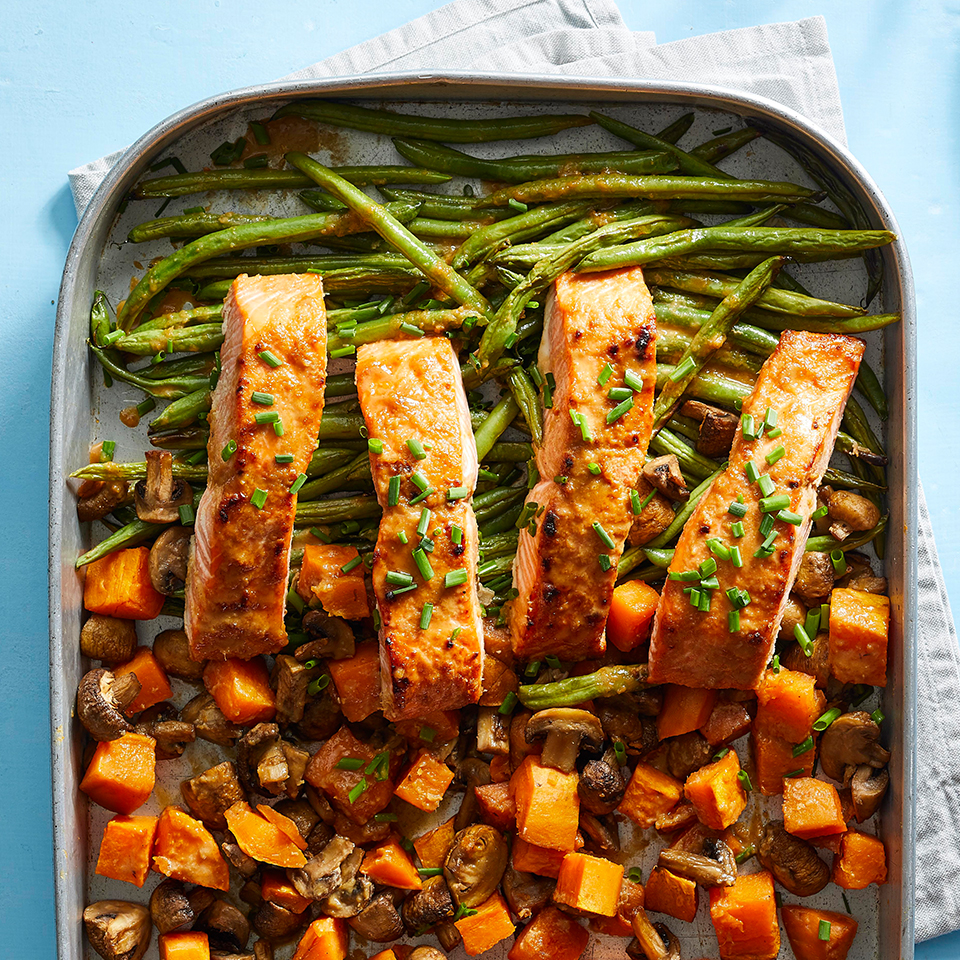 sheet pan of salmon and vegetables on blue background