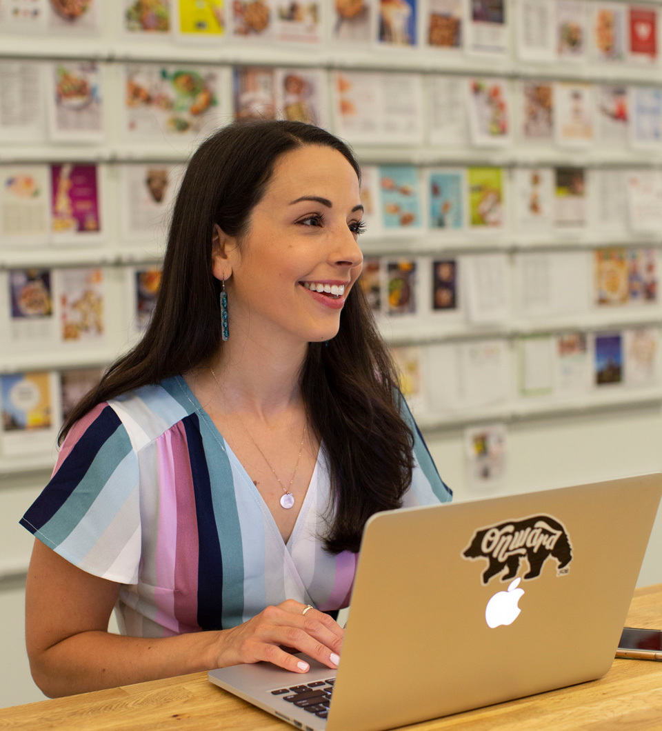 Woman with long dark hair in striped dress sits and types on a laptop in front of a magazine wall