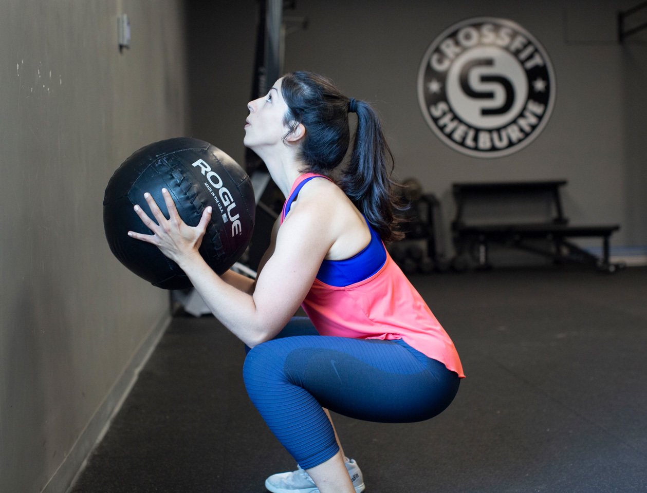 brunette woman squats with a ball at crossfit gym.