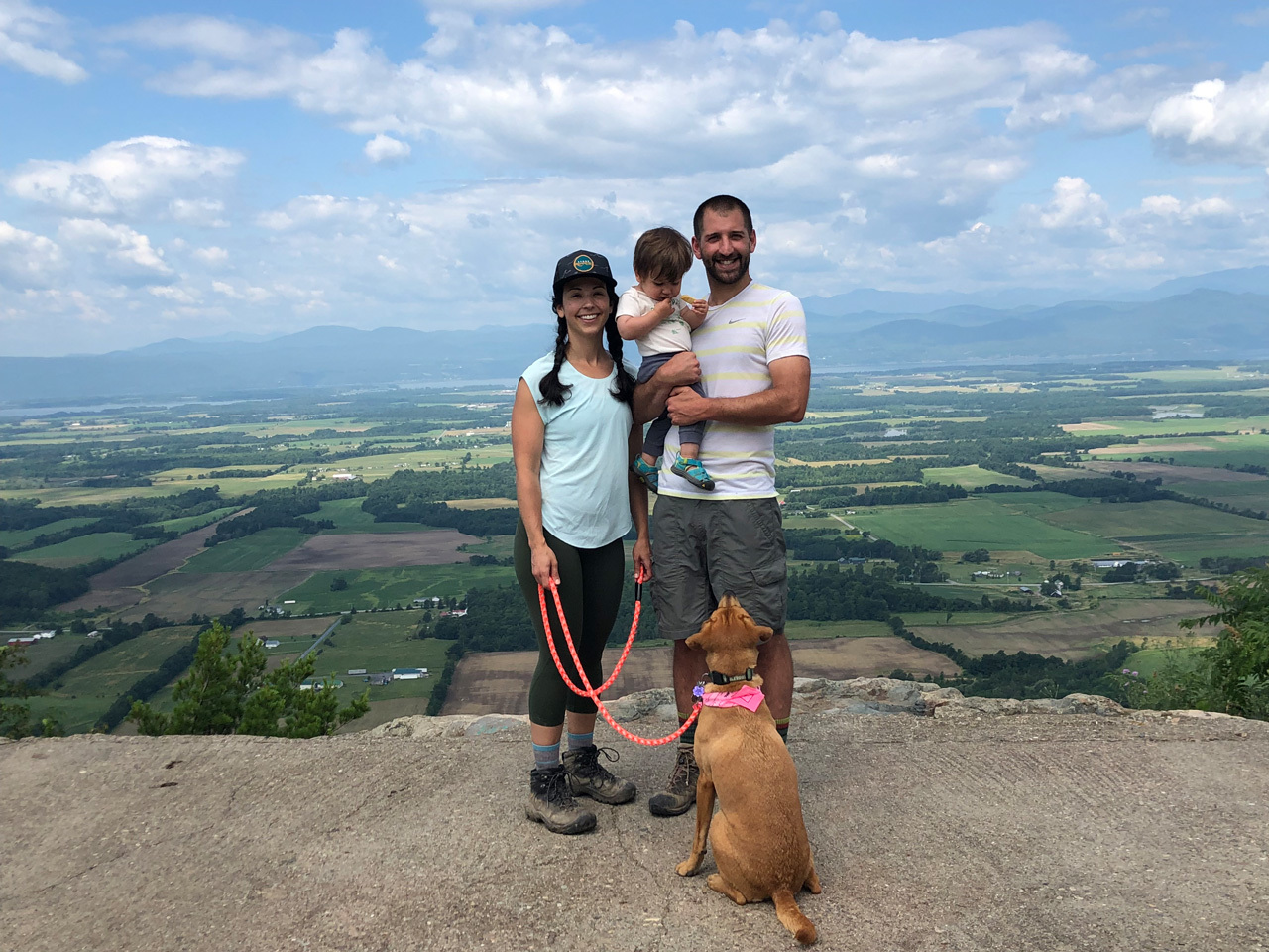 mom, son, dad and dog hiking in vermont, standing on top of mountain with view of farms and lake