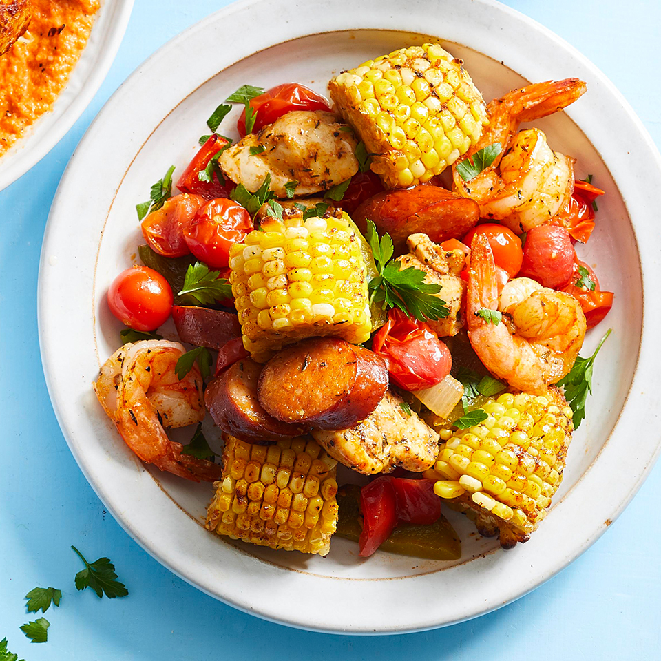 creole chicken and shrimp with corn and peppers and onions on white plate on blue background