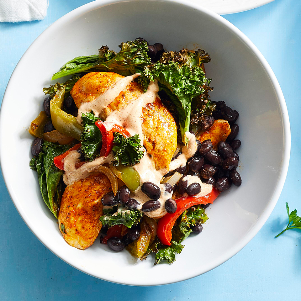 chicken fajita sheet pan dinner with black beans and greens in a white bowl on light blue background