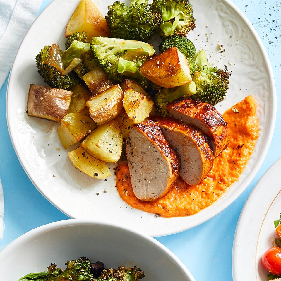 Pork, potatoes and broccoli on a white plate on a light blue background