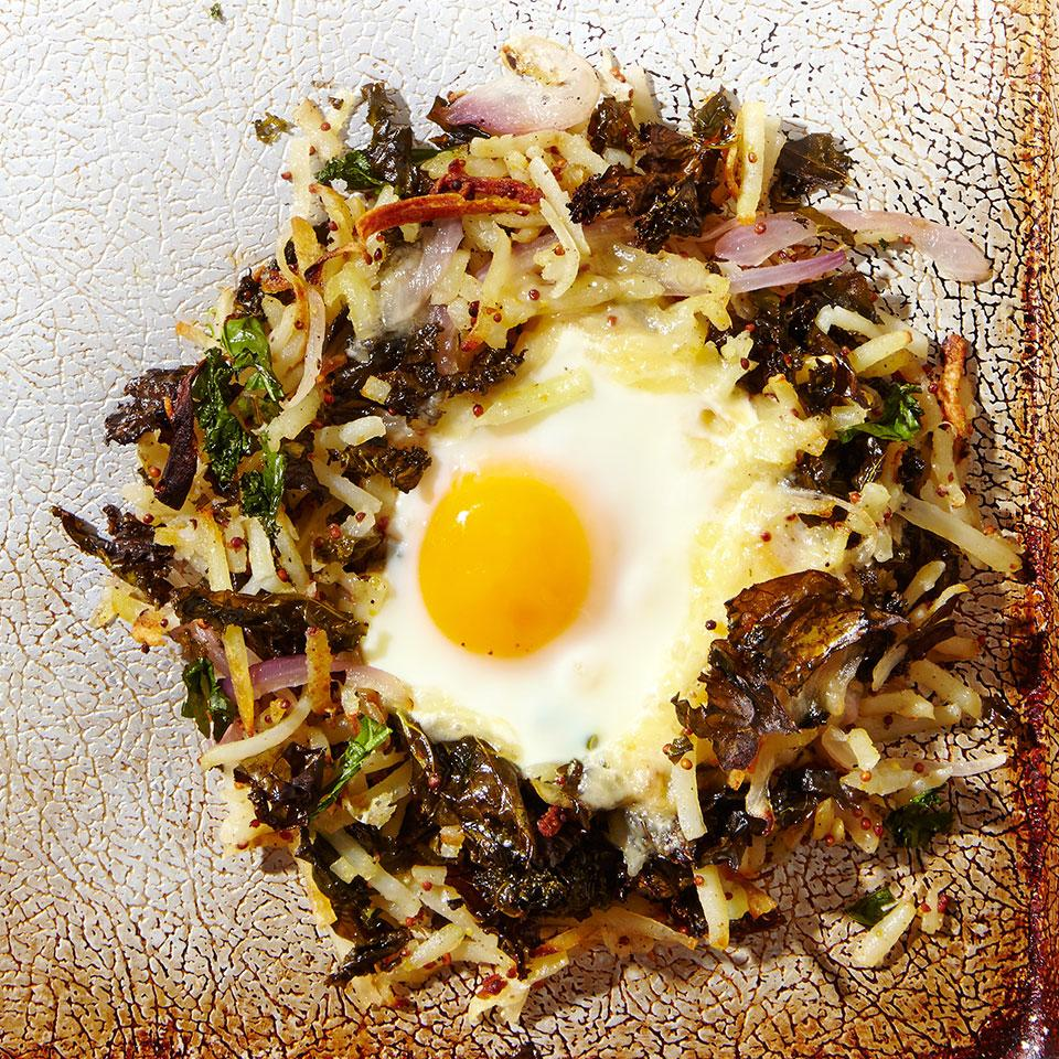 a circle of potato and kale hash with an egg in the center