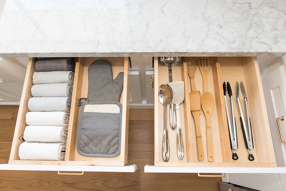 kitchen drawers with utencils, potholders and dish towels organized neatly
