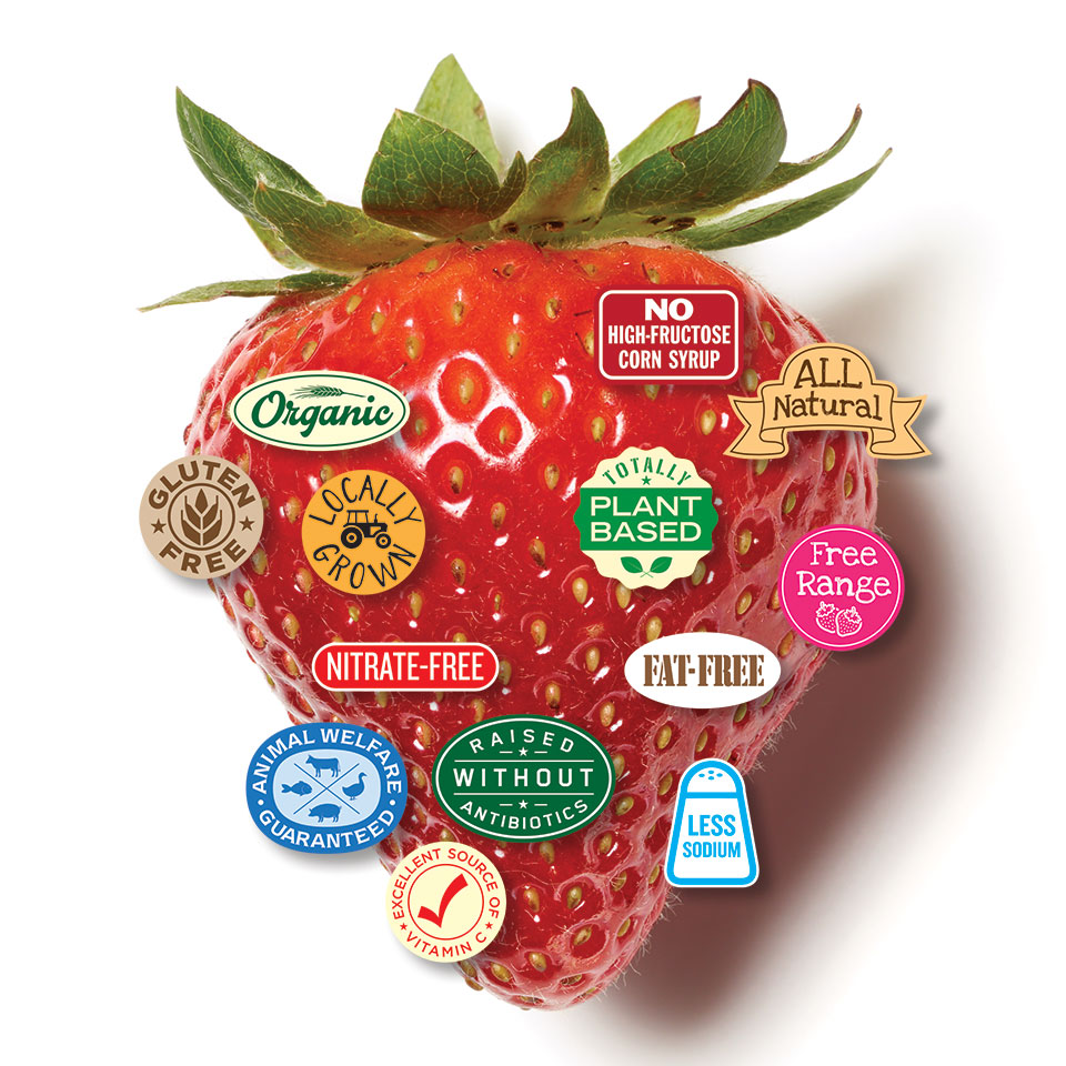 close up of strawberry with several label stickers on it - organic, gluten free, locally grown, all natural, etc.