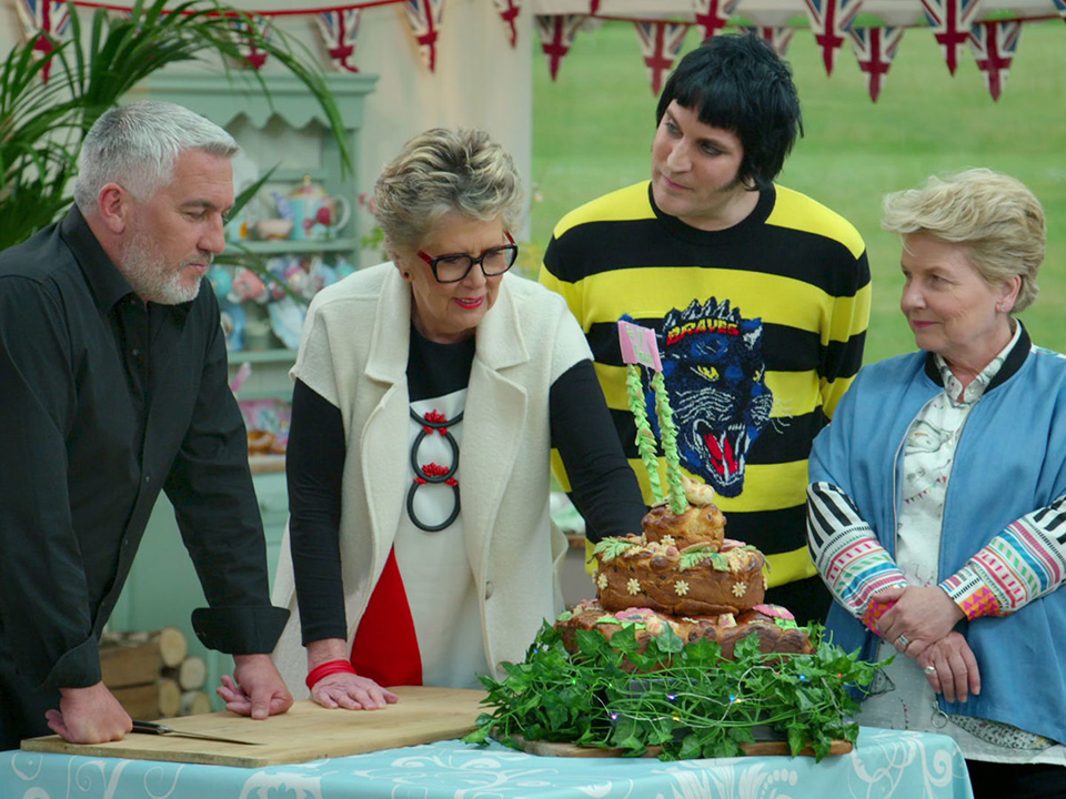 judges of The Great British Baking Show examining a large bread centerpiece